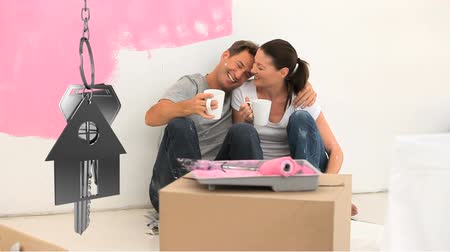 mülkiyet : Animation of silver house keys and house shaped key fob hanging with a young Caucasian man and woman painting a room of their new home in pink, embracing, drinking coffee and smiling in the background