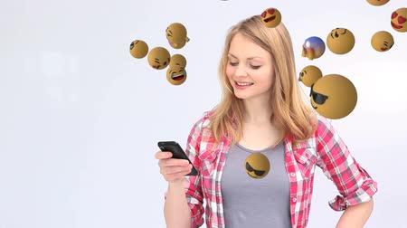 lol : Animation of emoji icons flying from right to left with a young Caucasian woman using a smartphone and showing a screen in the background