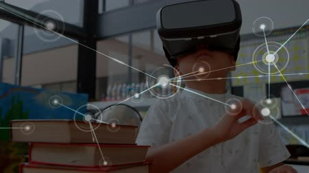 schoolkid : Animation of network of connections floating in the foreground with a Caucasian schoolboy wearing a VR headset, reaching out with his hands and looking around in the background Stock Footage