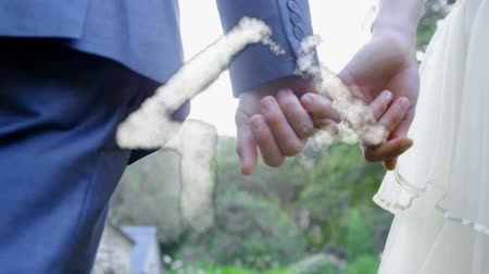 sen : Animation of a house shape made of cloud floating with a close up of a rear view of a Caucasian man and woman holding hands at their wedding in the background