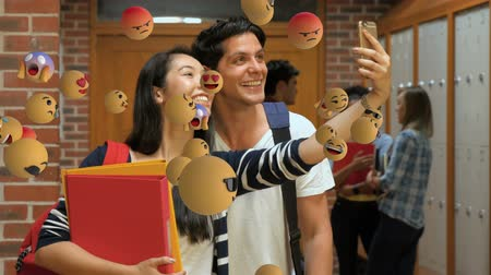 emoticon : Animation of emoji icons flying from left to right with male and female diverse students taking a selfie in the background