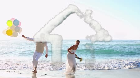 mülkiyet : Animation of a house shape made of cloud floating with a just married Caucasian man and woman on a beach holding balloons and flowers at their wedding in the background Stok Video