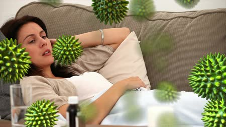 szczepienia : Animation of green 3d viruses with an ill Caucasian woman lying on a sofa and sneezing the background Wideo