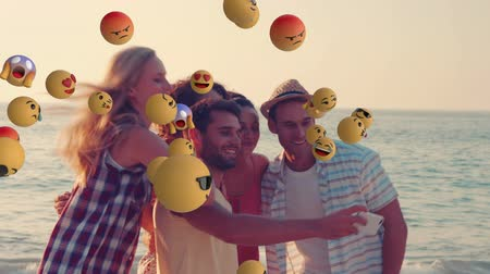emoticon : Animation of emoji icons flying from left to right with young multi ethnic male and female friends taking a selfie on a beach in the background Stock Footage