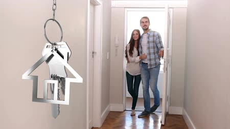 domy : Animation of silver house keys and house shaped key fob hanging with a young Caucasian man and woman entering their new home in the background