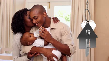 home life : Animation of silver house keys and house shaped key fob hanging with a young African American man and woman holding a baby and embracing in their new home in the background Stock Footage