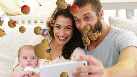 lol : Animation of emoji icons flying from left to right with a young Caucasian man taking a selfie with his family in the background Stock Footage