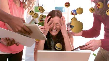 emoticon : Animation of emoji icons flying from right to left with a young stressed Caucasian woman using a laptop and screaming in the background Stock Footage
