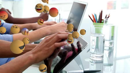 lol : Animation of emoji icons flying from left to right with hands of young multi-ethnic people using tablet and laptop in the background