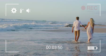 načasování : Animation of a young Caucasian couple walking on a beach holding hands, seen on a screen of a digital camera in record mode with icons and timer 4k Dostupné videozáznamy