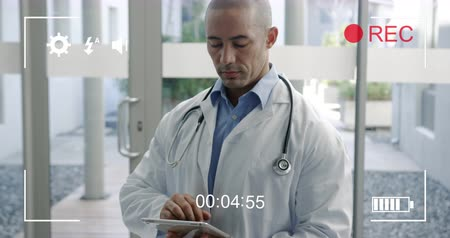 načasování : Animation of a portrait of a young mixed race male doctor looking to camera holding a tablet computer and talking, seen on a screen of a digital camera in record mode with icons and timer 4k