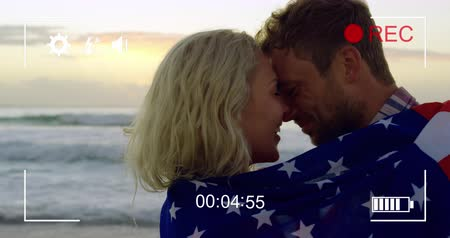 načasování : Animation of a close up of a young Caucasian couple on a beach wrapped in an American flag, seen on a screen of a digital camera in record mode with icons and timer 4k