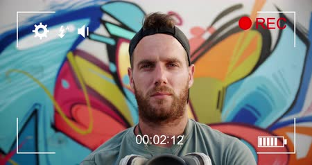 mode : Animation of a portrait of a young Caucasian man in front of graffiti, seen on a screen of a digital camera in record mode with icons and timer 4k