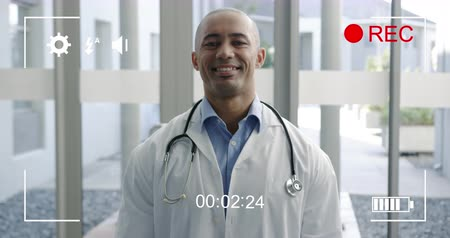 načasování : Animation of a portrait of a young mixed race male doctor smiling to camera, seen on a screen of a digital camera in record mode with icons and timer 4k Dostupné videozáznamy