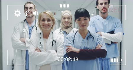načasování : Animation of a portrait of a diverse group of doctors looking to camera and smiling, seen on a screen of a digital camera in record mode with icons and timer 4k
