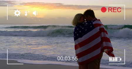 načasování : Animation of a young Caucasian couple on a beach wrapped in an American flag, seen on a screen of a digital camera in record mode with icons and timer 4k Dostupné videozáznamy