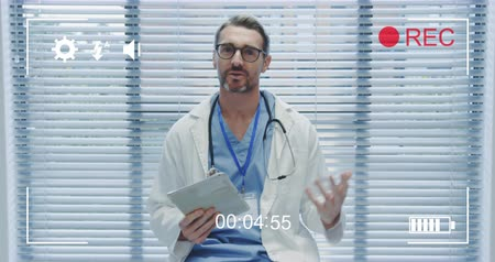 načasování : Animation of a portrait of a middle aged Caucasian male doctor looking to camera holding a tablet computer and talking, seen on a screen of a digital camera in record mode with icons and timer 4k