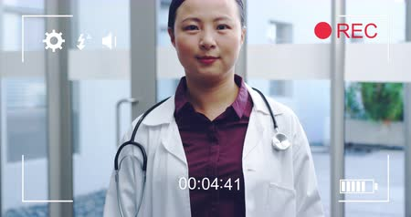 načasování : Animation of a portrait of a young Asian female doctor smiling to camera, seen on a screen of a digital camera in record mode with icons and timer 4k