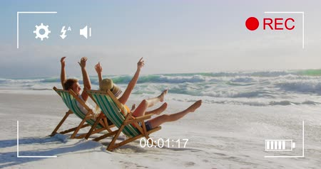 mode : Animation of a side view of a young Caucasian couple in deckchairs, seen on a screen of a digital camera in record mode with icons and timer 4k Stock Footage