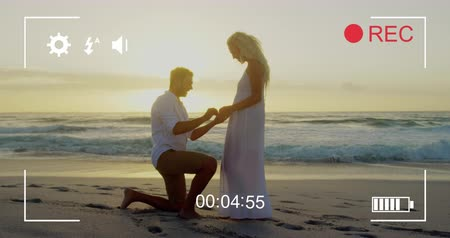 načasování : Animation of a young Caucasian man proposing to a young Caucasian woman, seen on a screen of a digital camera in record mode with icons and timer 4k