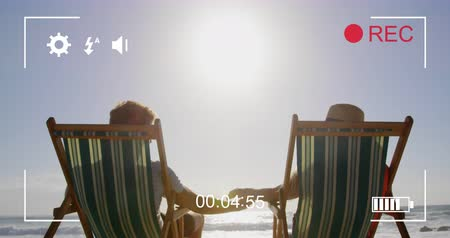 načasování : Animation of a rear view of a young Caucasian couple in deckchairs, seen on a screen of a digital camera in record mode with icons and timer 4k Dostupné videozáznamy