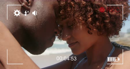 načasování : Animation of a close up of young African American couple, seen on a screen of a digital camera in record mode with icons and timer 4k