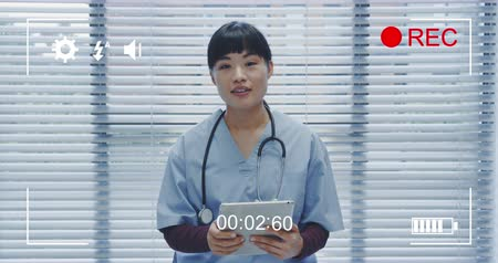 načasování : Animation of a portrait of a young Asian female doctor looking to camera holding a tablet computer and talking, seen on a screen of a digital camera in record mode with icons and timer 4k