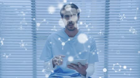 gelişme : Animation of a young Caucasian male scientist using a tablet and talking with molecules floating in the foreground