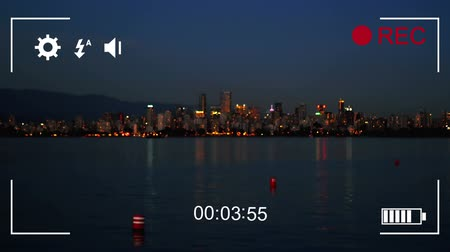 načasování : Animation of cityscape in the evening, seen on a screen of a digital camera in record mode with icons and timer