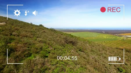 modo : Animation of countryside, seen on a screen of a digital camera in record mode with icons and timer Stock Footage