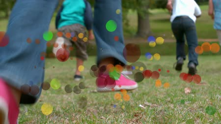 Animation of coloured spots of defocused twinkling light passing in front of young children running away from camera across a garden