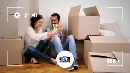 picture box : Animation of a young Caucasian man and woman drinking wine in their new home surrounded by boxes, seen on a screen of a smartphone in picture mode with icons in the foreground