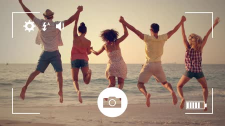 redőnyök : Animation of a rear view of a group of young multi-ethnic male and female friends holding hands and jumping on a beach, seen on a screen of a smartphone in picture mode with icons in the foreground Stock mozgókép