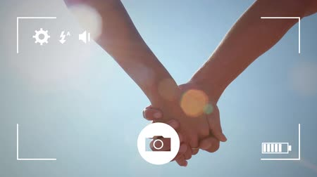 fondness : Animation of a young Caucasian man and woman holding hands, seen on a screen of a smartphone in picture mode with icons in the foreground