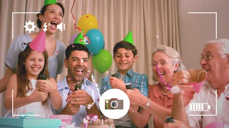 flama : Animation of a three generation Caucasian family at a birthday party releasing party streamers, seen on a screen of a smartphone in picture mode with icons in the foreground
