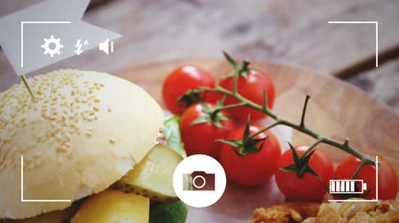 tomates cereja : Animation of a close up of a cheeseburger, fries, onion rings and cherry tomatoes, seen on a screen of a smartphone in picture mode with icons in the foreground