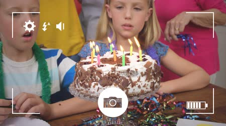 modo : Animation of a close up of pre teen Caucasian boy and girl blowing out candles on a birthday cake, seen on a screen of a smartphone in picture mode with icons in the foreground