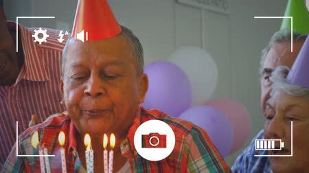 companionship : Animation of a close up of senior mixed race man blowing out candles on a birthday cake with a group of friends behind him, seen on a screen of a smartphone in picture mode with icons in the foreground