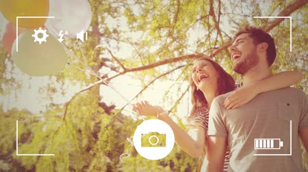 mode : Animation of a young Caucasian man and woman embracing and holding balloons, seen on a screen of a smartphone in picture mode with icons in the foreground