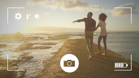 mode : Animation of a young mixed race man and woman walking on a beach holding hands, seen on a screen of a smartphone in picture mode with icons in the foreground