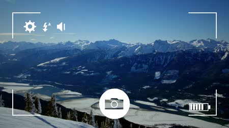 mode : Animation of snow covered mountains, seen on a screen of a smartphone in picture mode with icons in the foreground Stock Footage