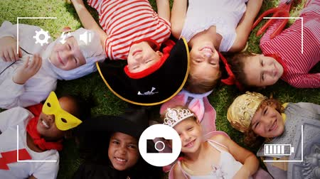 companionship : Animation of a overhead view of a group of multi-ethnic children in fancy dress costumes lying on a grass, seen on a screen of a smartphone in picture mode with icons in the foreground