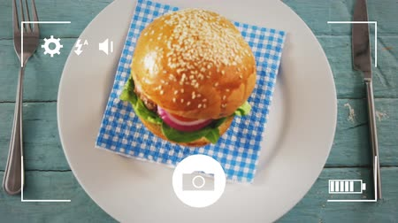 příbory : Animation of a close up of a hamburger on a plate, seen on a screen of a smartphone in picture mode with icons in the foreground