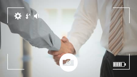 modo : Animation of a mid section of young Caucasian businessmen shaking hands, seen on a screen of a smartphone in picture mode with icons in the foreground