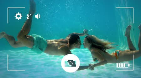 modo : Animation of a side view of a young Caucasian man and woman kissing and holding hands under water, seen on a screen of a smartphone in picture mode with icons in the foreground Stock Footage