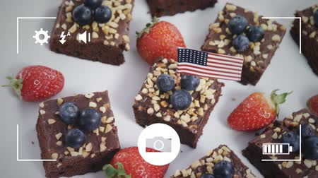 домовой : Animation of a close up of brownie cakes with strawberries and blueberries with American flags, seen on a screen of a smartphone in picture mode with icons in the foreground Стоковые видеозаписи