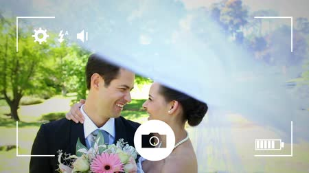fotolijst : Animation of a young Caucasian bride and groom kissing, seen on a screen of a smartphone in picture mode with icons in the foreground
