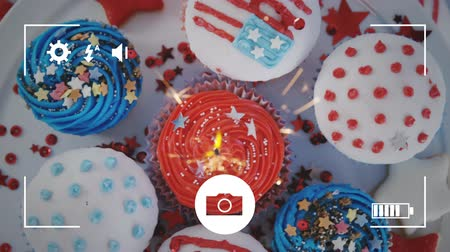 mode : Animation of a close up of cupcakes decorated with American flags and fireworks, seen on a screen of a smartphone in picture mode with icons in the foreground
