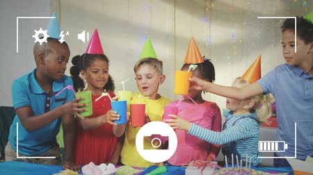 companionship : Animation of pre teen multi-ethnic children in party hats at a birthday party, seen on a screen of a smartphone in picture mode with icons in the foreground