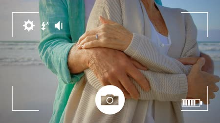 batteria : Animation of a mid section of a mature Caucasian man and woman embracing on a beach, seen on a screen of a smartphone in picture mode with icons in the foreground